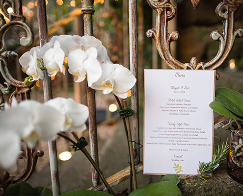 white orchids on rustic iron railing