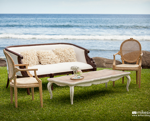 Shabby chic furniture on lawn beside the ocean